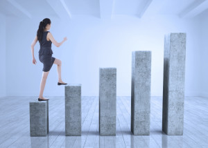 Businesswoman stepping up bar chart depicting growth